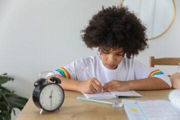 focused black schoolgirl doing homework at table in house