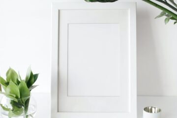 empty photo frame on desk decorated with green plants
