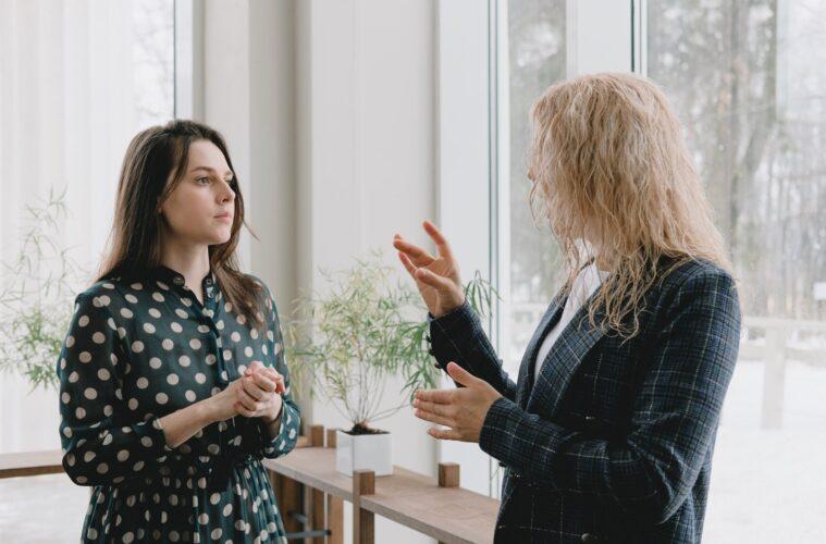 female coworkers talking beside glass windows